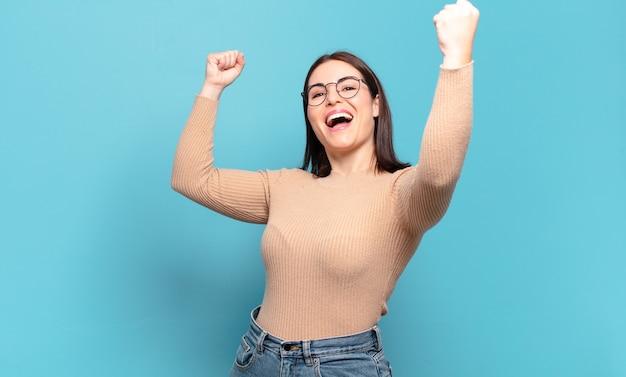 Молодая довольно непринужденная женщина триумфально кричит, выглядит взволнованной, счастливой и удивленной победительницей, празднует
