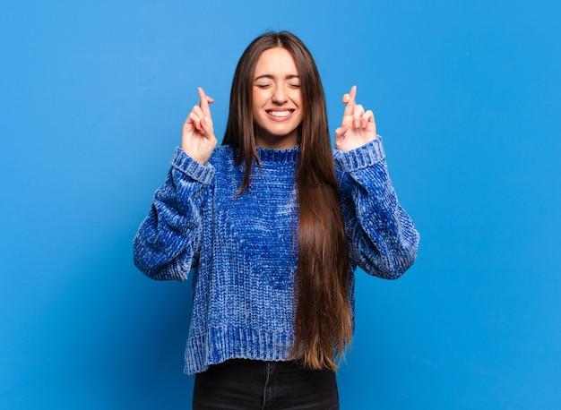 Молодая довольно непринужденная женщина улыбается и тревожно скрещивает оба пальца, чувствуя беспокойство и желая или надеясь на удачу