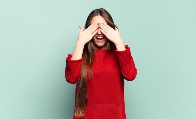 Молодая довольно непринужденная женщина улыбается и чувствует себя счастливой, прикрывая глаза обеими руками и ожидая невероятного сюрприза