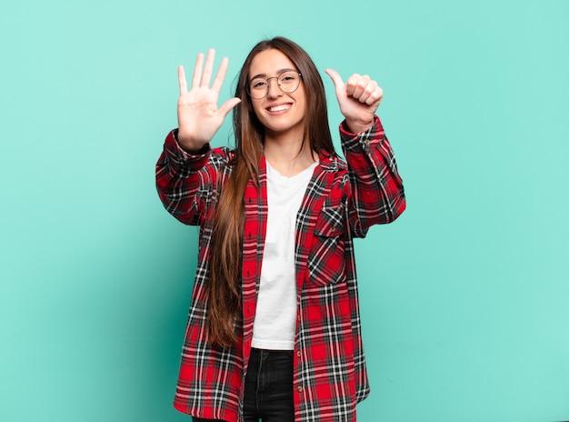 Молодая довольно непринужденная женщина улыбается и выглядит дружелюбно, показывает номер шесть или шестой рукой вперед, отсчитывая