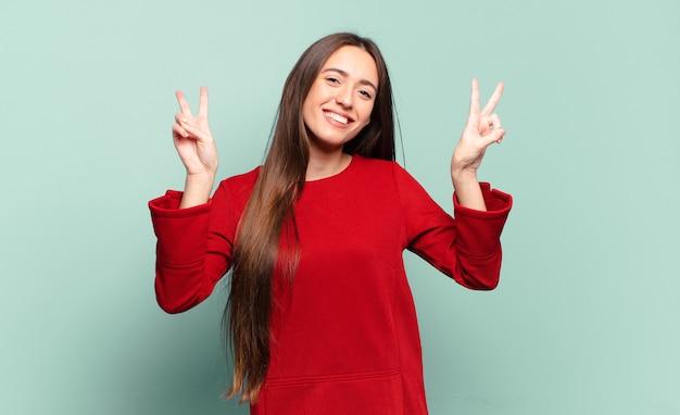 Молодая довольно непринужденная женщина улыбается и выглядит счастливой, дружелюбной и удовлетворенной, жестикулируя победу или мир обеими руками