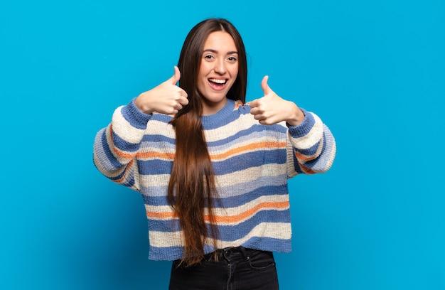 두 엄지 손가락으로 광범위하게 행복하고 긍정적이며 자신감 있고 성공적인 찾고 웃는 젊은 꽤 캐주얼 여성
