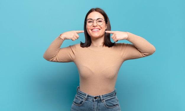 自信を持って笑顔の若いかなりカジュアルな女性は、自分の広い笑顔、前向きで、リラックスした、満足のいく態度を指しています