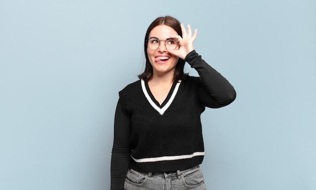 재미 있은 얼굴로 행복하게 웃고, 농담하고 구멍을 통해보고, 비밀을 염탐하는 젊은 꽤 캐주얼 여성