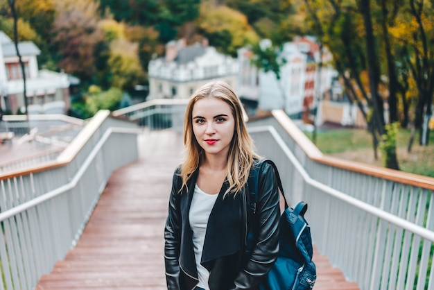 Молодая довольно небрежно одетая хипстерская девушка-турист позирует на улице у ступенек городского парка с рюкзаком