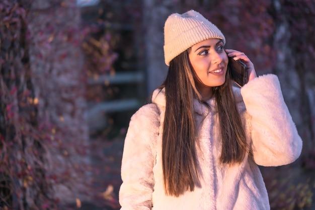 ピンクのウールのセーターと帽子をかぶって、電話で電話をかける街の若いかわいい白人ブルネット。ストリートスタイルのファッション