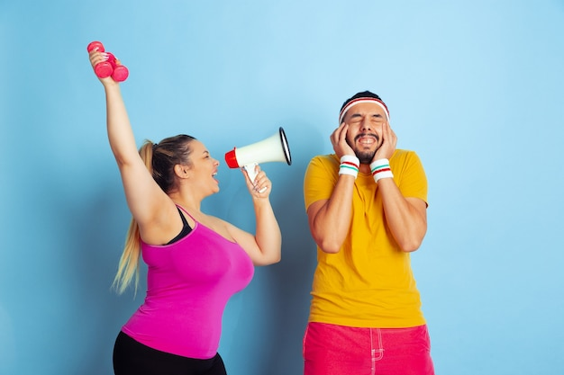 Young pretty caucasian couple in bright clothes training on blue background concept of sport, human emotions, expression, healthy lifestyle, relation, family. he's scared, she's calling in mouthpeace.