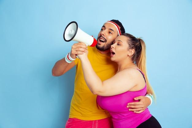 Giovane coppia piuttosto indoeuropea in abiti luminosi, formazione su sfondo blu concetto di sport, emozioni umane, espressione, stile di vita sano, relazione, famiglia. i saldi. chiamando insieme a bocca aperta.