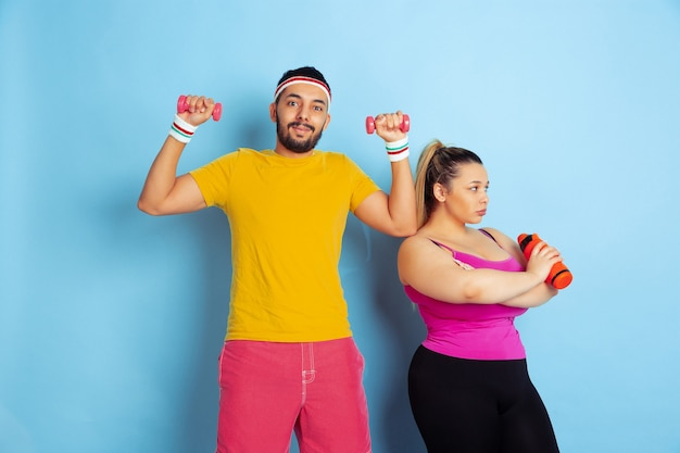 Giovane coppia piuttosto indoeuropea in abiti luminosi, formazione su sfondo blu concetto di sport, emozioni umane, espressione, stile di vita sano, relazione, famiglia. allenati con i pesi, divertiti.