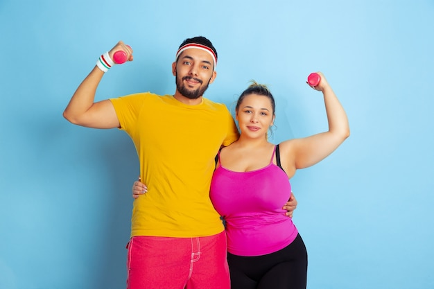 Young pretty caucasian couple in bright clothes training on blue space concept of sport, human emotions, expression, healthy lifestyle, relation, family