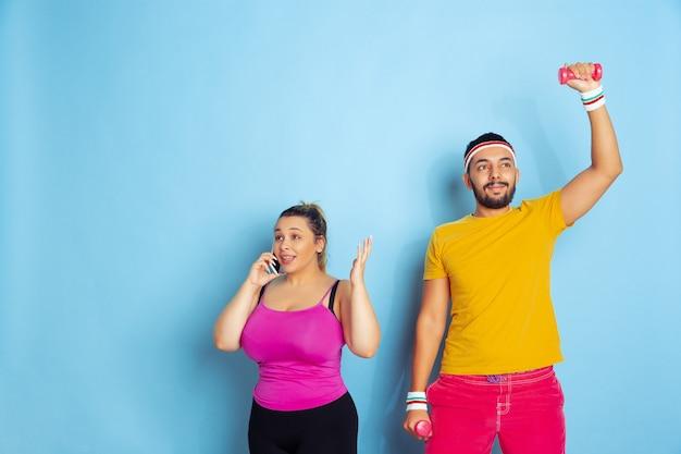 파란색 배경에 밝은 옷 훈련에 젊은 꽤 백인 부부 스포츠, 인간의 감정, 표현, 건강한 라이프 스타일, 관계, 가족의 개념. 그는 훈련 중이고 그녀는 전화 통화 중입니다.