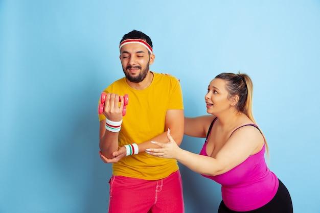 파란색 배경에 밝은 옷 훈련에 젊은 꽤 백인 부부 스포츠, 인간의 감정, 표현, 건강한 라이프 스타일, 관계, 가족의 개념. 무게로 훈련하고 재미있게 보내십시오.