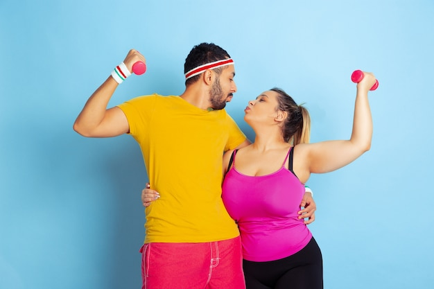 Молодая пара довольно кавказской в яркой одежде, обучение на синем фоне концепция спорта, человеческие эмоции, выражения, здоровый образ жизни, отношения, семья. тренируйтесь с отягощениями, получайте удовольствие.
