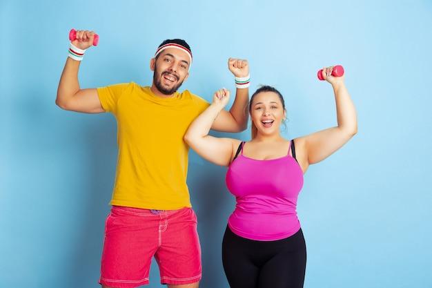 青い背景の明るい服のトレーニングで若いかなり白人のカップルスポーツ、人間の感情、表現、健康的なライフスタイル、関係、家族の概念。ウエイトトレーニング、楽しんでください。