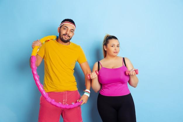 Молодая красивая кавказская пара в яркой одежде, тренирующейся на синем пространстве, концепция спорта, человеческие эмоции, выражение, здоровый образ жизни, отношения, семья
