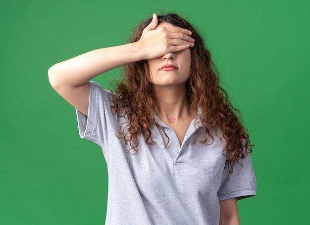 緑の壁で隔離の手で目を覆っている若いかなり白人の女の子