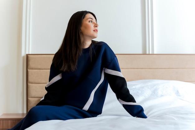寝室のベッドに座ってベッドに手を置いて横を見て若いかなり白人の女の子