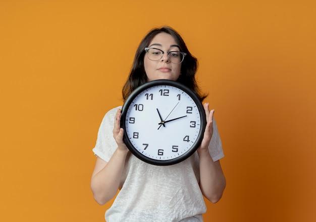 Молодая красивая кавказская девушка в очках держит и смотрит на часы, изолированные на оранжевом фоне с копией пространства