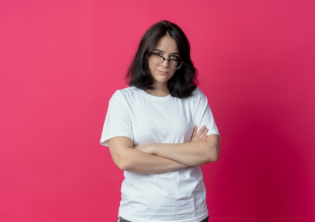 Young pretty caucasian girl wearing glasses standing with closed posture and looking at camera isolated on crimson background with copy space