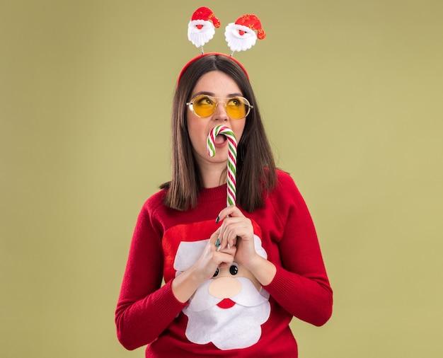 Молодая симпатичная кавказская девушка в свитере санта-клауса и ободке с очками держит традиционную рождественскую конфету возле рта