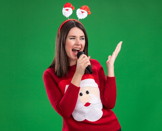 Young pretty caucasian girl wearing santa claus sweater and headband holding microphone looking at side keeping hand in air singing isolated on green wall with copy space