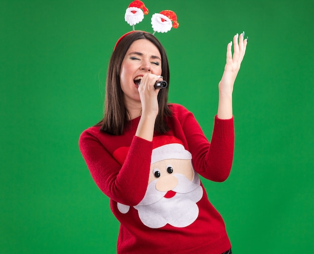 Young pretty caucasian girl wearing santa claus sweater and headband holding microphone raising hand singing with closed eyes isolated on green wall with copy space