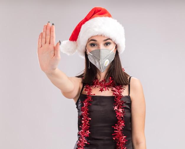 Молодая красивая кавказская девушка в шляпе санта-клауса и гирлянде из мишуры защитной маски на шее, глядя в камеру, делает стоп-жест, изолированные на белом фоне