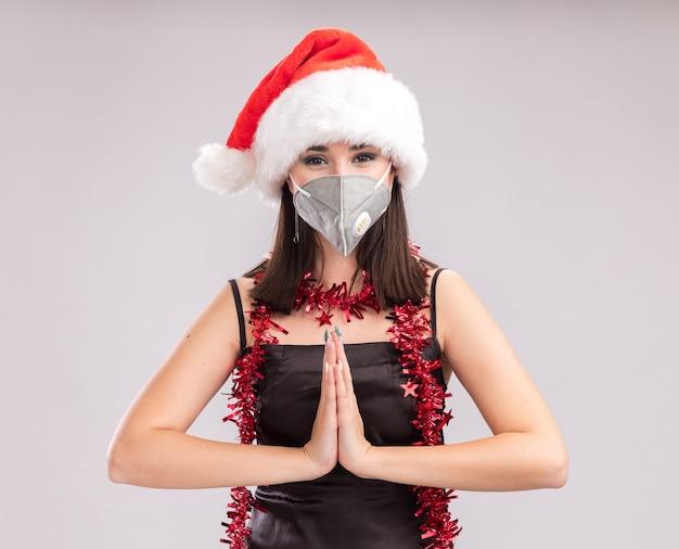 サンタの帽子と保護マスクの見掛け倒しのガーランドを首の周りに身に着けている若いかなり白人の女の子は、白い背景で手を一緒に隔離してカメラを見て