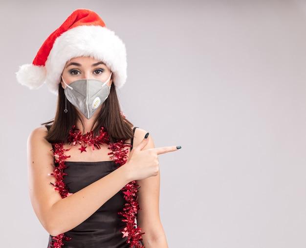 サンタの帽子と保護マスクの見掛け倒しのガーランドを首の周りに身に着けている若いかなり白人の女の子は、コピースペースで白い背景で隔離された側を指しているカメラを見て