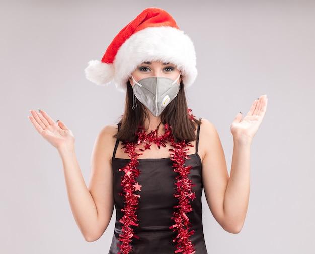 サンタの帽子と保護マスクの見掛け倒しのガーランドを首の周りに身に着けている若いかなり白人の女の子は、白い背景で隔離の空の手を示すカメラを見て