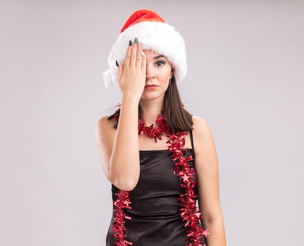 복사 공간 흰색 배경에 고립 된 얼굴의 절반을 덮고 카메라를보고 목에 산타 모자와 반짝이 갈 랜드를 입고 젊은 예쁜 백인 여자