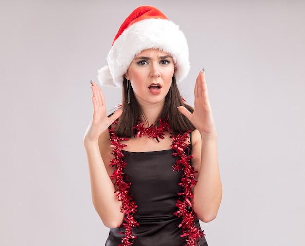 サンタの帽子と見掛け倒しのガーランドを首に身に着けている若いかわいい白人の女の子は、コピースペースで白い背景に隔離された何かを説明する空中に手を置いてカメラを見ています