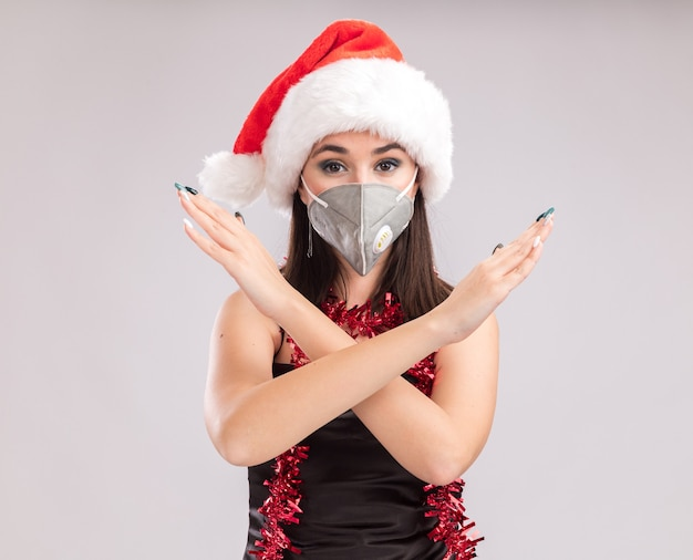 Young pretty caucasian girl wearing santa hat and protective mask tinsel garland around neck looking at camera doing no gesture isolated on white background