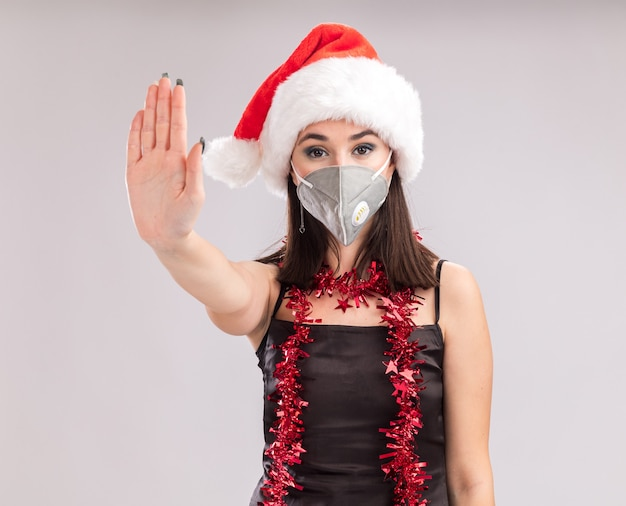 Young pretty caucasian girl wearing santa hat and protective mask tinsel garland around neck looking at camera doing stop gesture isolated on white background