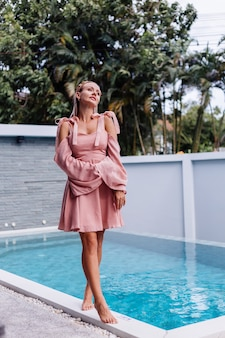 Young pretty caucasian romantic woman alone in summer cute dress on vacation at luxury villa