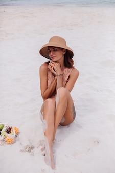 Giovane donna in forma abbronzata abbastanza caucasica in vestiti a maglia e cappello sulla spiaggia