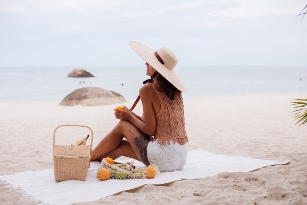 Young pretty caucasian tanned fit woman in knitted clothes and hat on beach