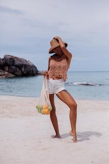 Giovane donna in forma abbronzata abbastanza caucasica in vestiti lavorati a maglia sulla spiaggia tropicale che indossa il cappello di paglia che tiene il sacchetto di stringa riutilizzabile ecologia pieno di frutta mela arancia uva