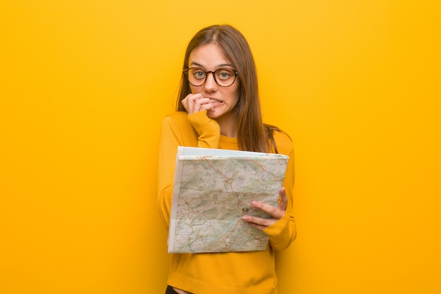 Young pretty caucasian woman biting nails, nervous and very anxious. she is holding a map.