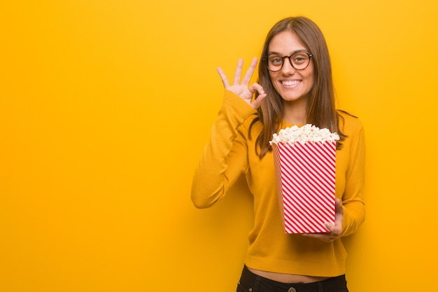 若いかなり白人の女性は陽気で自信を持って大丈夫なジェスチャーをしています。彼女はポップコーンを食べています。