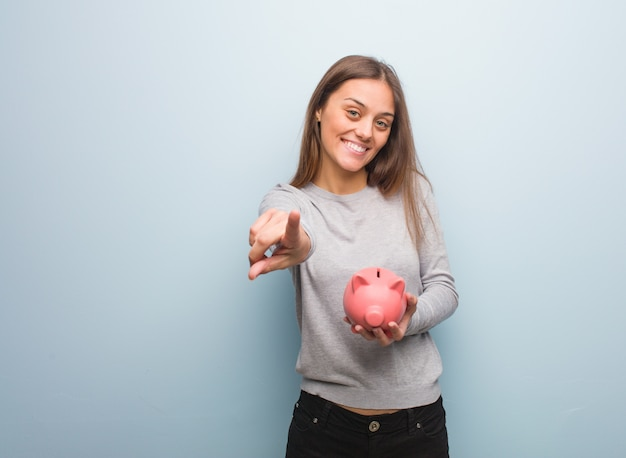 Young pretty caucasian woman cheerful and smiling pointing to front. she is holding a piggy bank.