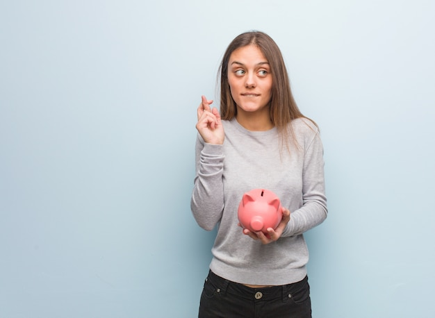 Young pretty caucasian woman crossing fingers for having luck. she is holding a piggy bank.