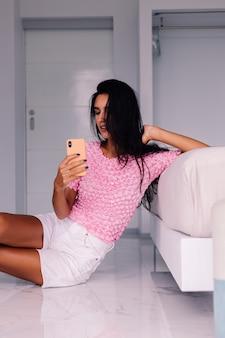 Giovane blogger di moda donna abbastanza caucasica che indossa abiti eleganti, prendendo selfie foto