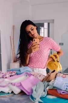 Giovane blogger di moda donna abbastanza caucasica che indossa abiti eleganti, prendendo foto