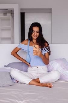 Молодая красивая кавказская женщина модный блоггер в стильной одежде, фотографируя