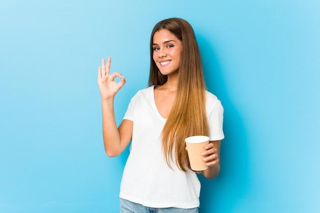 若いかなり白人女性持ち帰り用のコーヒーを保持している陽気で自信を持ってokのしぐさを示しています。