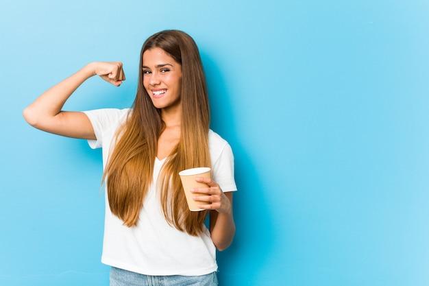 Молодая симпатичная кавказская женщина, держащая кулак повышения кофе на вынос после победы, концепции победителя.