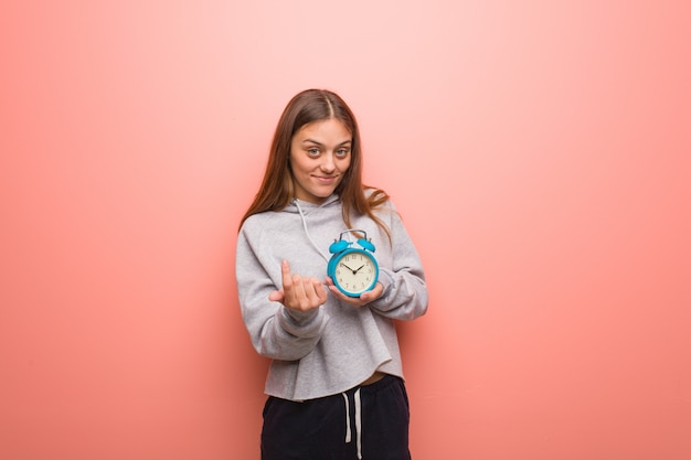Young pretty caucasian woman inviting to come. she is holding an alarm clock.
