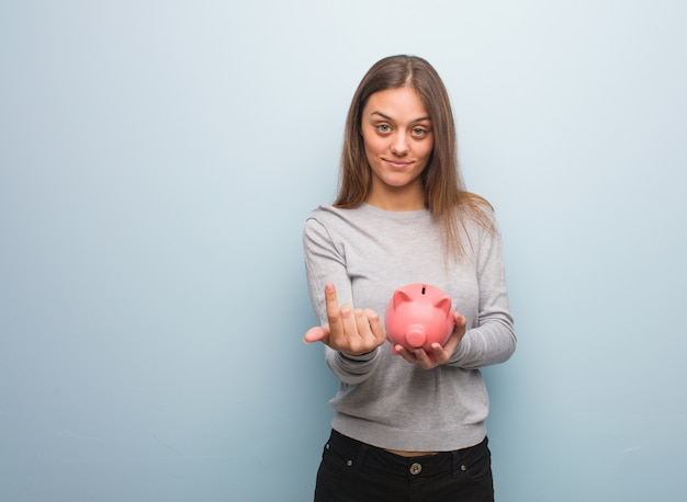 Young pretty caucasian woman inviting to come. she is holding a piggy bank.