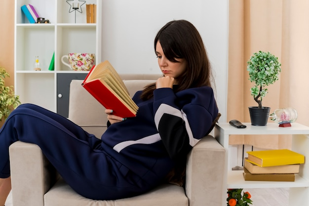 Young pretty caucasian woman sitting on armchair in designed living room touching chin holding and reading book